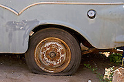 Old dilapidated car with a flat tire
