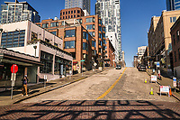 """Pike Place & Pine Street is vacant, thus providing a bold  prominence of the shadow created by the large letters of the """"Public Market"""" sign at the intersection in the foreground. (March 21, 2020)."""