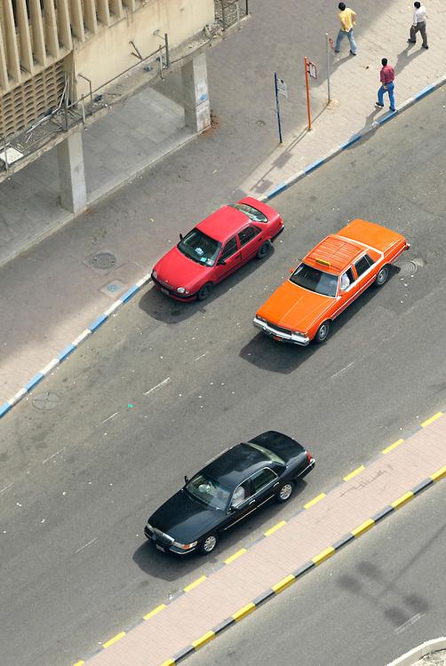KWT; Kuwait City, Städtische Szene von Oben, Drei Männer überqueren eine Strasse, Drei vorbeifahrende Autos und drei Schilder einer Bushaltestelle, Abgerissene Elektrokabel auf einem Dach       Kuwait City scene from above, Three men crossing a street next to a bus stop while three cars just passed     