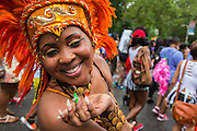 A costumed woman with an orange headdress blows a kiss.