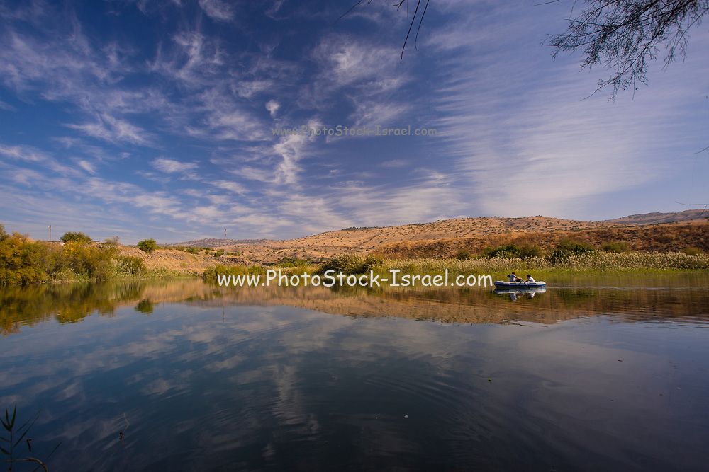 2 people rowing in an inflatable rubber dinghy in a natural water pond. Photographed at the Ein Afek nature reserve, Israel