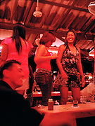 Waitresses and bartenders dance for a customer at a beer bar.