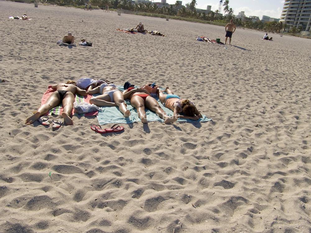 group of girls sunbathing on the beach Miami USA