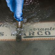 A nman walks during high tide on a touristic sign in St Mark Square San Marco is one of the six sestieri of Venice, lying in the heart of the city.