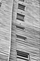 Windows along the side of a modern building as seen from the high line park walkway in New York City