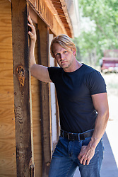 blond man in a black tee shirt leaning against a rustic shed
