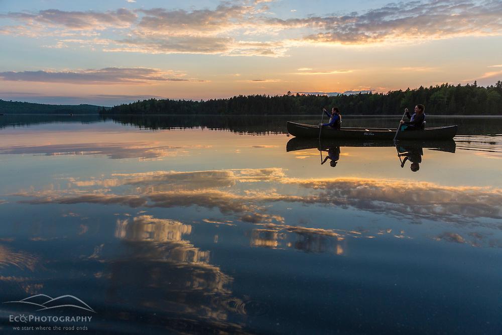 Two women canoe on Long Pond near the Appalachian Mountain Club's Gorman Chairback Lodge. Maine's 100 Mile Wilderness.