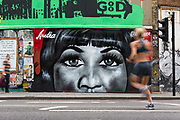 A woman jogger runs past new street art graffiti in Shoreditch, east London, England on August 19, 2018 that pays tribute to the singer, Aretha Franklin who has died following a battle with pancreatic cancer.  The mural has been created by artist, Jules Muck in collaboration with Global Street Art.