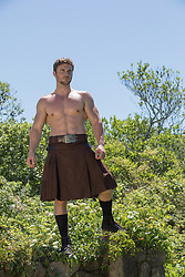 muscular man without a shirt in a kilt outdoors