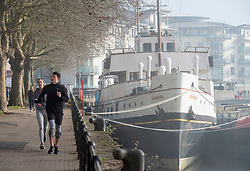 © Licensed to London News Pictures; 27/02/2021; Bristol, UK. People take exercise around Bristol Harbourside and past the ship Balmoral on a misty morning while in lockdown during the covid-19 coronavirus pandemic. The forecast is for bright sunny weather. Photo credit: Simon Chapman/LNP.