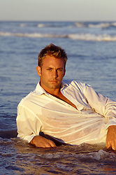 portrait of a handsome man in a white shirt lounging in the ocean at sunset