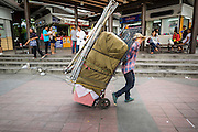 29 MAY 2014 - BANGKOK, THAILAND: A Thai street vendor hauls away her shop after police ordered her and other street vendors to leave the area around Victory Monument. After a series of protests around Victory Monument earlier in the week, the Thai army Thursday shut down vehicle access to the area, one of the main intersections in Bangkok, and kept people out of the area. Thousands of soldiers surrounded the Monument and effectively locked the area down. There were no protests at Victory Monument for the first time in the week since the coup deposed the elected civilian government.   PHOTO BY JACK KURTZ