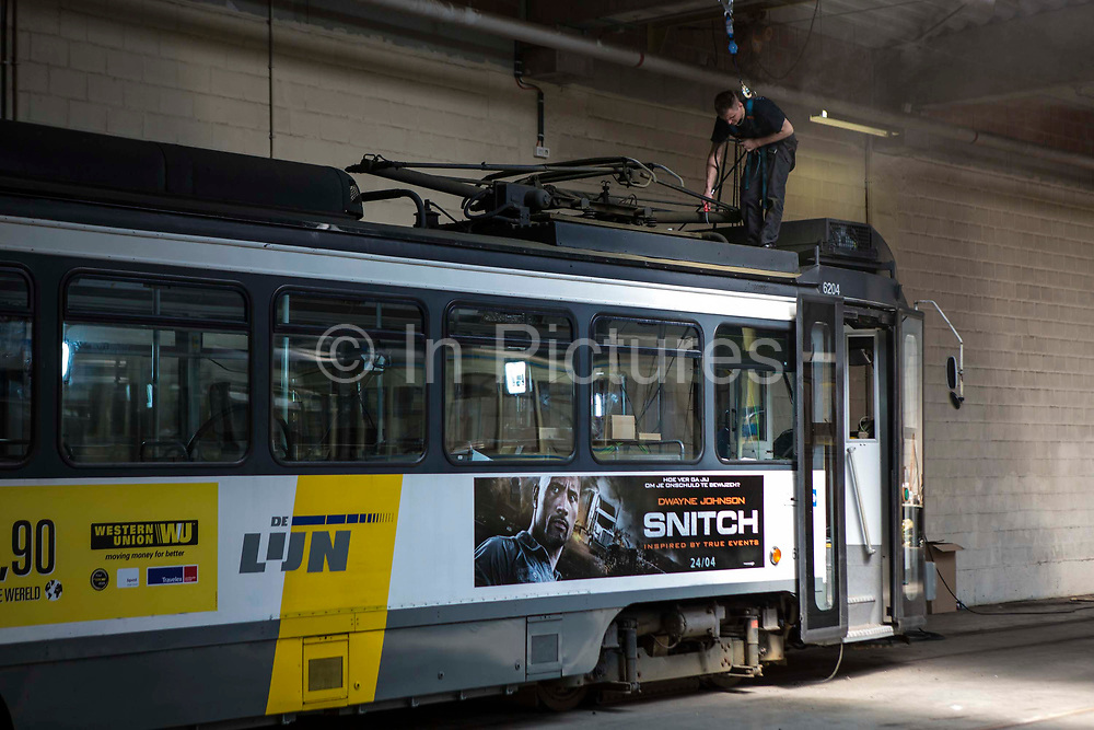 A male engineer stands on the tramcar roof to carry out maintenance on a De Lijn electric tram in the depot in Gentbrugge, Ghent, Belgium.