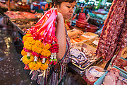 "03 OCTOBER 2012 - BANGKOK, THAILAND:      A flower vendor walks from market stall to market stall selling garlands in Khlong Toey Market in Bangkok. Khlong Toey (also called Khlong Toei) Market is one of the largest ""wet markets"" in Thailand. Thousands of people shop in the sprawling market for fresh fruits and vegetables as well meat, fish and poultry every day.       PHOTO BY JACK KURTZ"