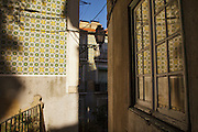 Ceramic tiles facade reflected on a window at Alfama district in Lisbon.