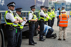 London, UK. 6 September, 2019. Metropolitan Police officers monitor a truck making a delivery to ExCel London beneath which an activist is locked in protest against DSEI, the world's largest arms fair. The road remained blocked for several hours. The fifth day of protests was themed as Stop The Arms Fair: Stop Climate Change in order to highlight links between the fossil fuel and arms industries.