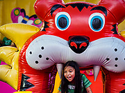 24 NOVEMBER 2018 - BANGKOK, THAILAND:  A child in a bouncy castle on the midway at the Red Cross Fair. The Red Cross Fair is a fund raiser and an annual event in Bangkok that draws thousands of attendees every night of its nine day run. The fair features games of chance, a midway with rides, handicrafts and food. This is the first year the fair has been in Lumpini Park. Previously it had been held in the Dusit section of Bangkok. The 2018 Fair marks 125 years of service for the Red Cross in Thailand.    PHOTO BY JACK KURTZ