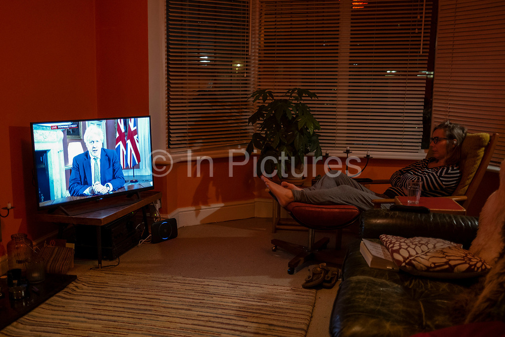 Woman watches a tv in a living room in Moseley as Prime Minister Boris Johnson announces a new national coronavirus lockdown during a live television address on 4th January 2021 in Birmingham, United Kingdom. Following the recent surge in cases including the new variant of Covid-19, this nationwide lockdown, which is an effective Tier Five, will come into operation on 6th January, with all citizens to follow the message to stay at home to save lives.