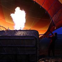 Africa, Kenya, Masai Mara. Preparing hot air balloon for flight as flame fills balloon.