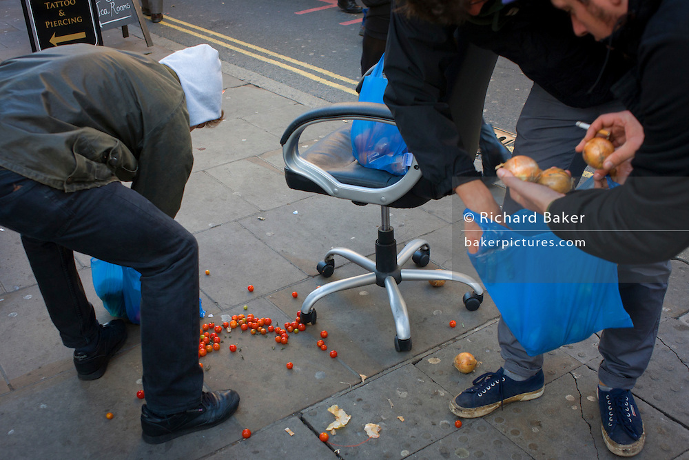 Shoppers in the street pick-up dropped tomatoes and onions.