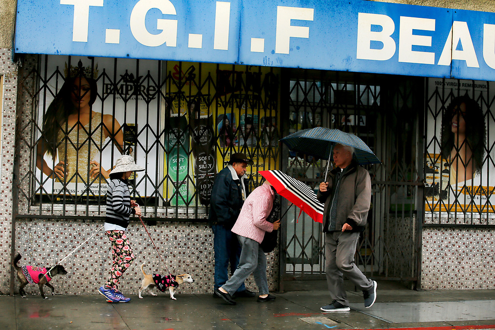 People make their way through the rain along San Bruno Avenue on Sunday, Feb. 3, 2019, in San Francisco, Calif.