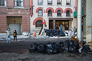 Black refuse garbage bags pile up after severe snow along South Side Street, Lower Manhattan, New York City, New York, United States of America.