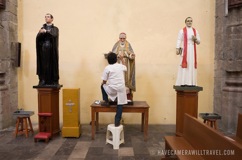 A technician undertakes careful restoration and preservation work on some of the many statues in Iglesia de la Santisima Trinidad in Mexico City, Mexico. Iglesia de la Santisima Trinidad translates as Church of the Holy Trinity.