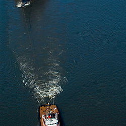 Aerial view of the Crowley's Patriarch tugboat pulling the USS Seattle south down the Delaware River back to Washington State for dismantling