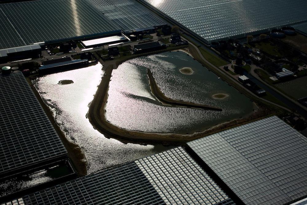 Nederland, Zuid-Holland, Westland, 20-03-2009; nieuw aangelegd waterbassin in Polder het Nieuwland tussen 's-Gravenzande en Hoek van Holland, omgeving Maasdijk. Het bassin dient om de toevloed van regenwater van de omringende kassen op te vangen. Op deze wijze wil men wateroverlast in het kassengebied voorkomen. Door de dammen en eilandjes ziet het bassin er uit als een glimlachend gezichtje. Aan de rand staat watermolen De Nieuwlandsche molen. Glinstering van zonlicht op het water. Air view on newly constructed pond in the Nieuwland Polder between 's-Gravenzande and Hoek van Holland. The smiley-like pond is used for the drainage of rainwater, on the border a drainage mill. Sparkling sunshine reflects on the water..Swart collectie, luchtfoto (toeslag); Swart Collection, aerial photo (additional fee required); .foto Siebe Swart / photo Siebe Swart