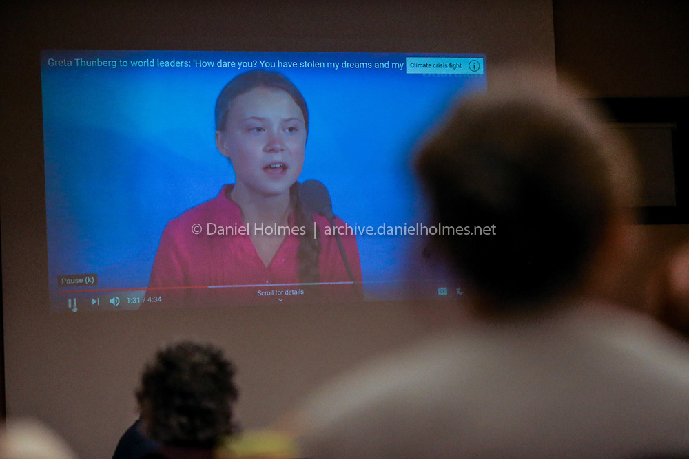 (9/25/19, NATICK, MA) Audience members watch a video of Swedish environmental activist Greta Thunberg during the panel discussion on climate change at the Natick Senior Community Center on Wednesday. [Daily News and Wicked Local Photo/Dan Holmes]