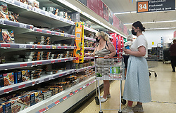 © Licensed to London News Pictures. 21/07/2021. London,  UK. Shoppers wearing face coverings in Sainsbury's superstore in London. On Freedom Day, wearing face coverings while shopping in Sainsbury's became a personal choice but the supermarket encourages customers to continue wearing a face covering. Sainsbury's is asking customers to shop 'one adult per household' to help manage the number of shoppers in store at any one time.<br /> Photo credit: Dinendra Haria/LNP