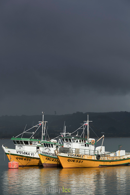 View of fishing boats on sea in harbor under overcast sky, Chiloe Island, Chile