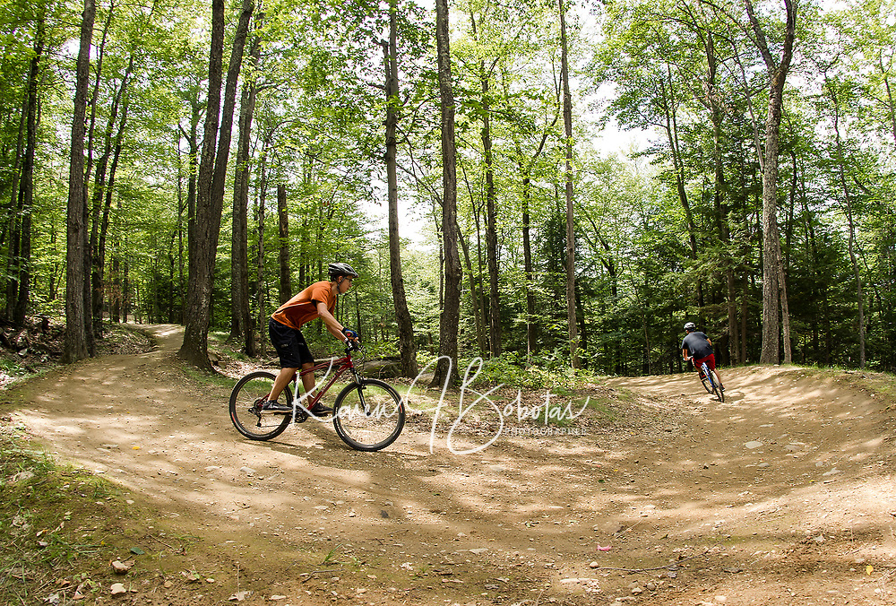 """Riders cruise down the """"Freedom Trail"""" at Highland Mountain Bike Park in Northfield on Wednesday afternoon.  (Karen Bobotas/for the Laconia Daily Sun)"""