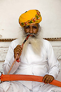 Indian man with beard looking at camera, in traditional Rajastani dress smoking a pipe, Jodhpur fort, Jodhpur, Rajastan, India. .