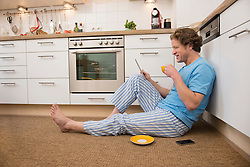 Man in pajama using digital tablet in kitchen