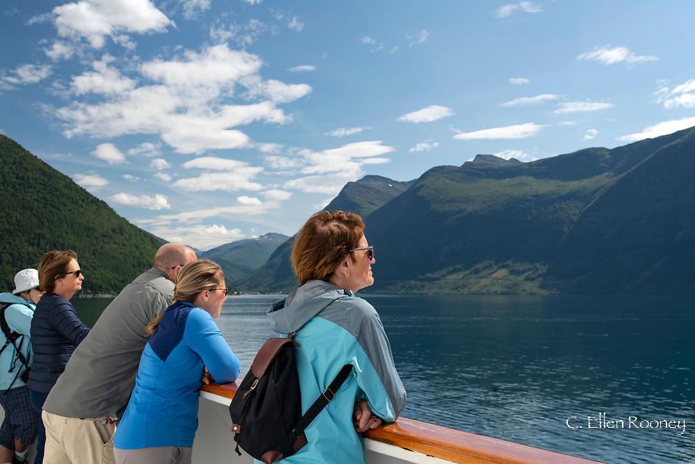 Passengers enjoying the scenery during a Hurtigruten cruise through Geiranger Fjord, Vestlandet, Norway