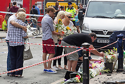 © Licensed to London News Pictures . FILE PICTURE DATED 15/07/2013 . Oldham Street , Manchester , UK . Mum Susan and stepfather Wilf lay flowers at the scene . Stephen Hunt's family at the scene . Son Sam (maroon shorts , 15), brother Christopher (white t-shirt, jeans, close cropped hair), grandmother Ruth (blue check shirt, dark trousers , red sunglasses), mother Susan (blue top, beige slacks, sunglasses), stepfather Wilf (dark hair, black t-shirt, grey shorts), daughter Charlotte (black and white sleeveless top, black pants, 18), sister Sarah (cream sleeveless top, blue jeans, dark hair, sunglasses) and ex-wife Zoe (white top, black pants, sunglasses) . The scene on Oldham Street following a fire at Paul 's Hair World on 13th July which claimed the life of fireman Stephen Hunt . Photo credit : Joel Goodman/LNP
