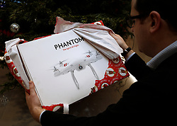 PICTURE POSED BY MODEL. A drone is unwrapped as a Christmas present. Britons given drones for Christmas have been warned they could face prosecution for flying them dangerously.