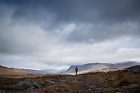 Silhouette of female hiker looking north in Alisvagge along Kungsleden trail, Lappland, Sweden