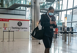 © Licensed to London News Pictures. 20/10/2020. London, UK. A flight attendant walks past a testing centre at Heathrow Terminal 5. A one hour Covid-19 testing centre at London Heathrow for Hong Kong and Italy passengers has opened up at London Heathrow. Two facilities one at Terminal 5 and the other at Terminal 2 will offer much quicker results than the NHS as samples don't need to be sent away to be tested. Prime Minister Boris Johnson is expected to announce a Tier 3 lockdown for Manchester tonight as coronavirus levels of infections continue to escalate throughout the UK. Photo credit: Alex Lentati/LNP