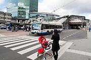 Een vrouw belt terwijl ze met een kind in een kinderwagen bij een zebrapad wacht tot een stadsbus is gepaseerd. In Utrecht wordt het centraal station grondig verbouwd. Momenteel is de tweede fase afgerond. De reizigers zullen nog tot 2016 last hebben van de verbouwing.<br /> <br /> A woman is on the phone while she is waiting with a child in a stroller for a bus to pass by. In Utrecht the central station is reconstructed. At this moment the second stage has finished. The travelers will be faced with inconveniences until 2016.