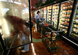 01 Feb 2006. Uptown, New Orleans, Louisiana.  Post Katrina. <br /> The Whole Foods supermarket reopens amidst great celebration 5 months after  the city was hit by Hurricane Katrina. A shopper reaches into the freezer on the frozen food section.<br /> Photo; Charlie Varley/varleypix.com
