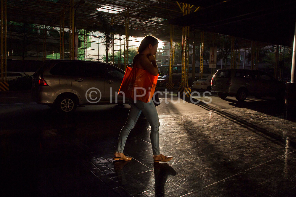 Woman walking under a scaffolding structure on Palm Drive, Makati in Manila, Philippines.