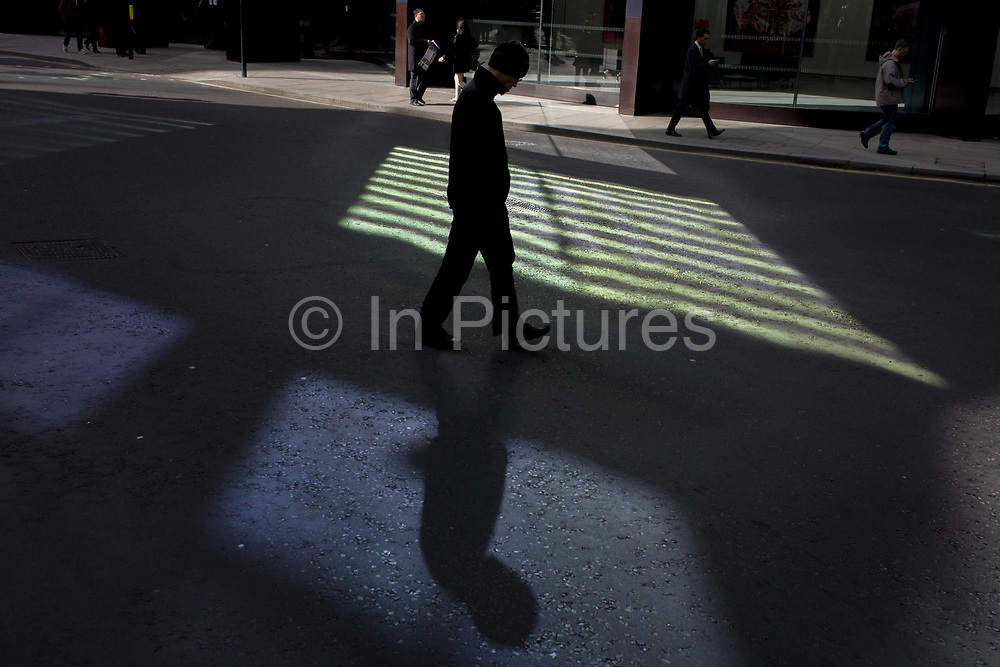 A downcast male pedestrian walks through reflected light shining from a City of London office building. Walking slowly at his own speed, the person looks downbeat, a downward-looking character in the bustle of the modern city. He walks past the pool of bright reflective lighting the City of London, known as the Square Mile after its ancient Roman walled past. They will continue through Royal Exchange Buildings in EC2, the heart of the capital's financial district.