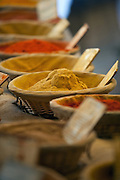 Fresh spices for sale are lined up on a table at a market in Gordes, France