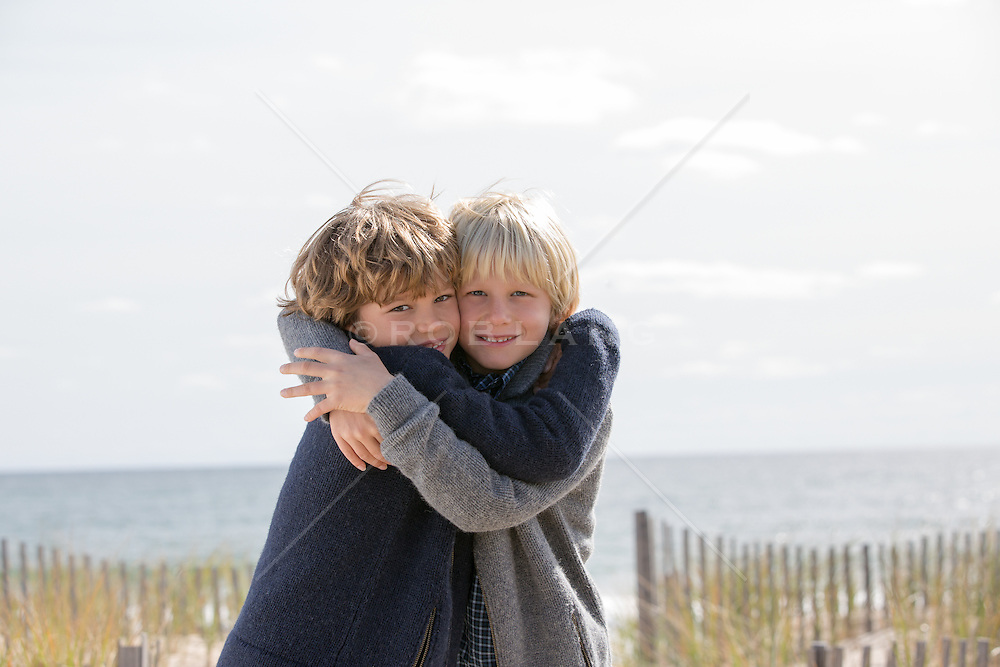 twin boys hugging outdoors at the ocean in The Fall season