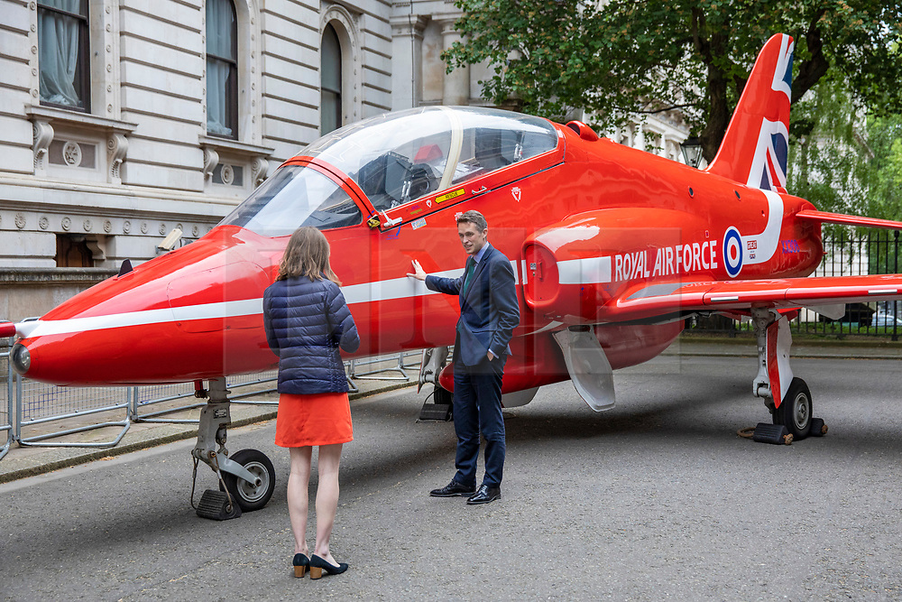 © Licensed to London News Pictures. 23/05/2018. London, UK. Defence Secretary Gavin Williamson (R) stands in front of a Royal Air Force (RAF) Red Arrow jet on Downing Street as part of the RAF100 Centenary celebrations. Photo credit: Rob Pinney/LNP