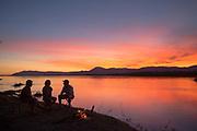 Tourists talking by river at sunset, Zambezi River, Zambia