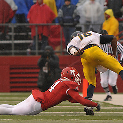 Dec 5, 2009; Piscataway, NJ, USA; Rutgers cornerback David Rowe (4) tackles West Virginia quarterback Jarrett Brown (16) during second half NCAA Big East college football action in West Virginia's 24-21 victory over Rutgers at Rutgers Stadium.