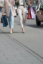 Low section of two mature women shopping in the city, Bavaria, Germany